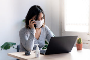 young quarantined woman talking on the phone wearing medical face mask and with hand sanitizer working from home office due to corona virus outbreak