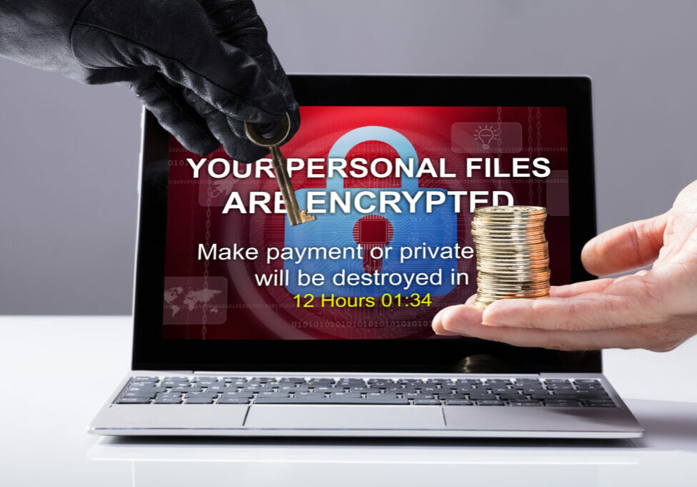 Person's Hand Giving Coins To Hacker In Exchange Of Security Key In Front Of Laptop