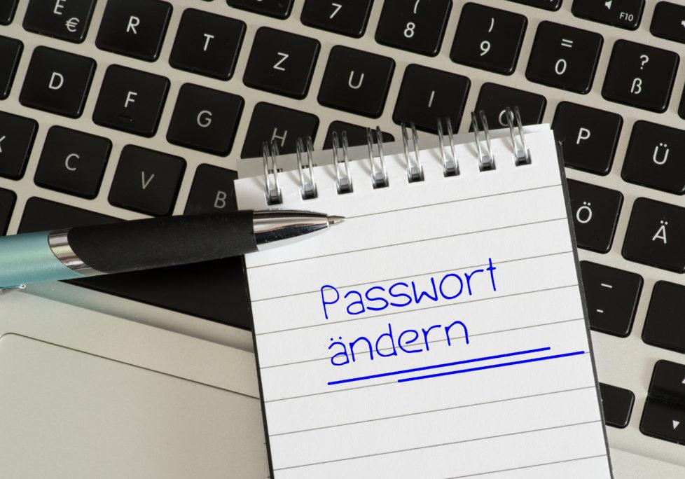 Ein Laptop und eine Notiz mit dem Hinweis an Passwort Änderung